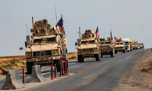 A convoy of US military vehicles, arriving from northern Iraq, drives along a road in the countryside of Syria's north-eastern city of Qamishli on 26 October 2019.