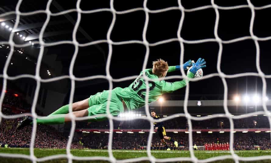 Caoimhin Kelleher dives to his right to deny Arsenal's Dani Ceballos in the penalty shootout.