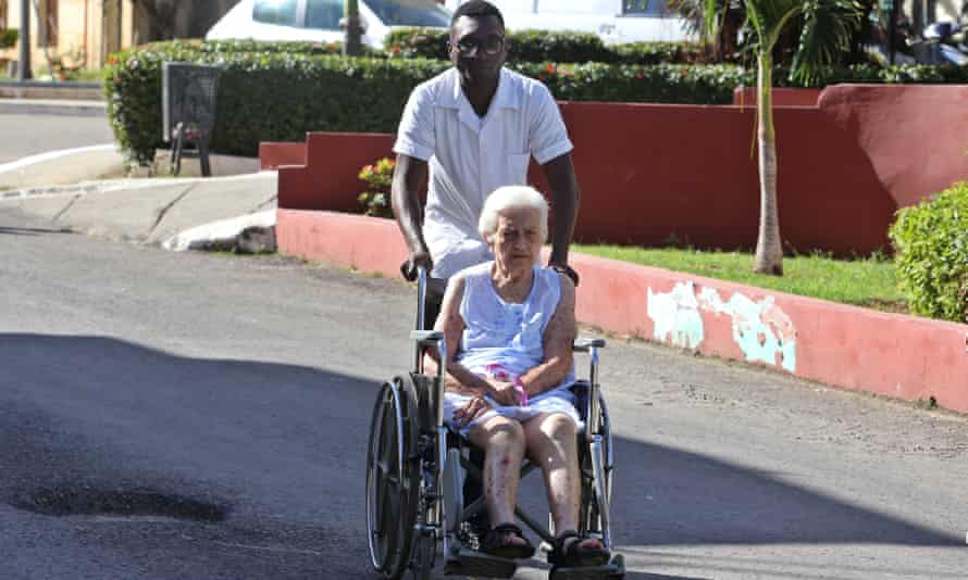 A health worker helps a lady in a wheelchair at the Calixto Garcia hospital, in Havana, Cuba, on Wednesday. Cuba reported that it is withdrawing from the More Doctors in Brazil due to the 'threatening and derogatory' words of President-elect Jair Bolsonaro.
