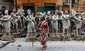 A woman walks past semi-finished clay idols of Hindu mythological characters that are being made for the upcoming Kali Puja festiva in Kolkata, India