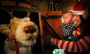 An elf helper, holding a baby, points towards a toy reindeer in Santa's Grotto at Walby Farm Park, Lake District.