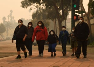 A family wearing masks walk through streets near the Thomas fire in Ventura