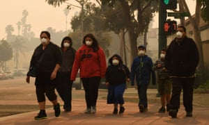 a family wearing face masks in the smoke-filled streets of ventura california
