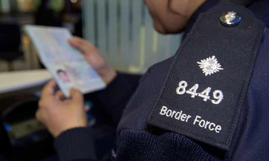 A Border Force officer checks the passport of a passenger at Heathrow airport.