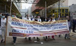 Healthcare workers hold placards and banners protesting at the Greek government's handling of the pandemic.