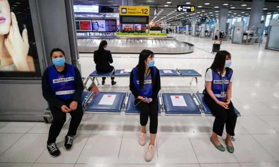 Socially distancing airport staff wearing face masks at Suvarnabhumi airport in Bangkok