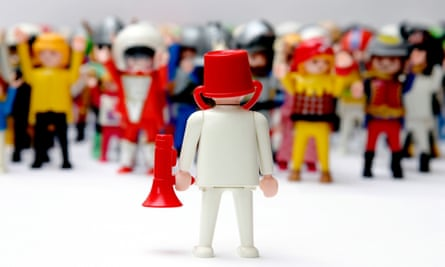 playmobil man wearing bucket on head and loudhailer addressing crowd of figures