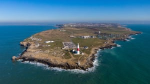 Portland, UK. Early spring weather over Portland Bill lighthouse, Dorset, which was first used on 11 January 1906