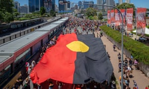 a giant Aboriginal flag at an Invasion day march