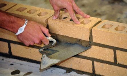 A trainee bricklayer lays bricks with a trowel