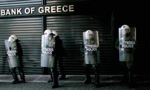 在抗议紧缩措施的总罢工期间,防暴警察在希腊国家银行封闭的分支机构外排队。