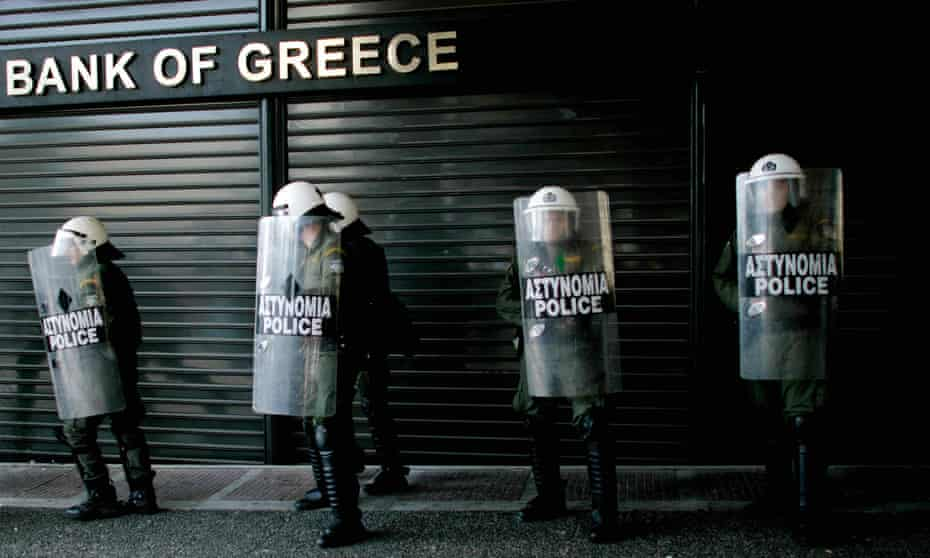 Riot police line up outside a closed branch of the National Bank of Greece during a general strike in protest against austerity measures .