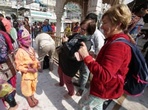 Tourists take photos of a child dressed as Lord Krishna at Durgiana Temple, Amritsar