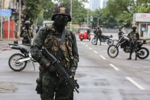 Soldiers stand at a checkpoint after the government announced an island-wide lockdown