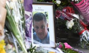 A picture of Keith Palmer among flowers near the Houses of Parliament.