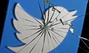 Twitter logo is seen through broken glass