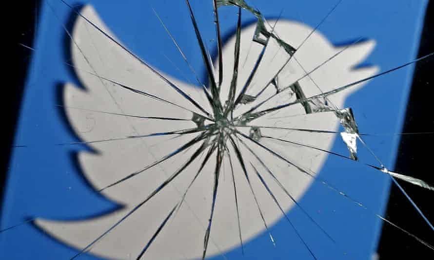 A 3D-printed Twitter logo is seen through broken glass