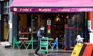 A waiter carries chairs and tables at a cafe in Kuzguncuk district of Istanbul, Turkey