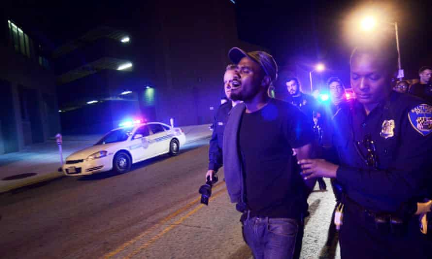 A man is led away by Baltimore police on Saturday night. The man claimed he was on his way home when he was arrested.