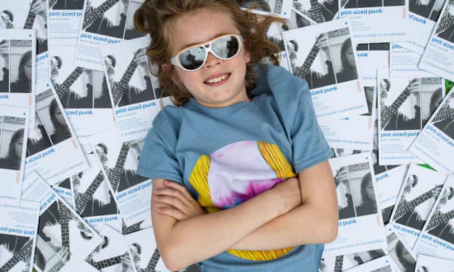 Arlo Lippiatt in sunglasses, surrounded by copies of his music fanzine, Pint-Sized Punk.