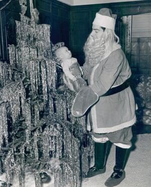 Joe DiMaggio playing Santa Claus with his newborn son Joseph Paul DiMaggio III in 1941