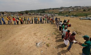 Locals give out food after a fire in an South African township