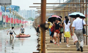 People walk across a temporary bridge over a flooded road in Wuhan, China.
