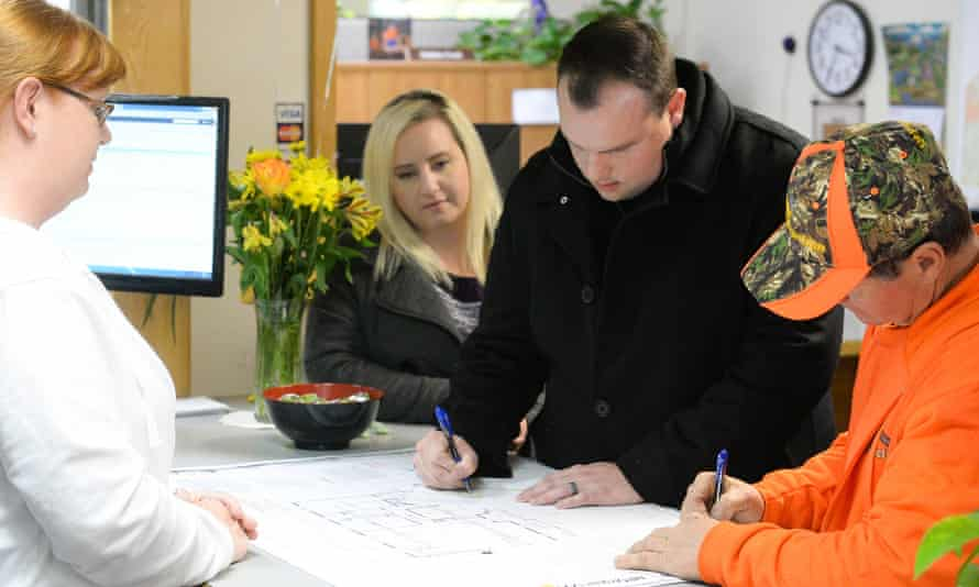 Jason Buzzard, center, and his contractor Jon Hornback, right, sign their permit paperwork as Meagann Buzzard (left) watches at Paradise town hall on 28 March.