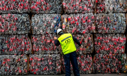A recycling technician in front of stacks of pressed plastic bottles