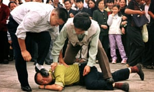 Police detain a Falun Gong protester in Tiananmen Square as a crowd watches in Beijing, in 2000.