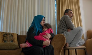 Nseen Ghazoul holds her granddaughter Shahed Daleh while sitting next to her husband, Naief Ghazoul, in Charlottesville, Virginia.