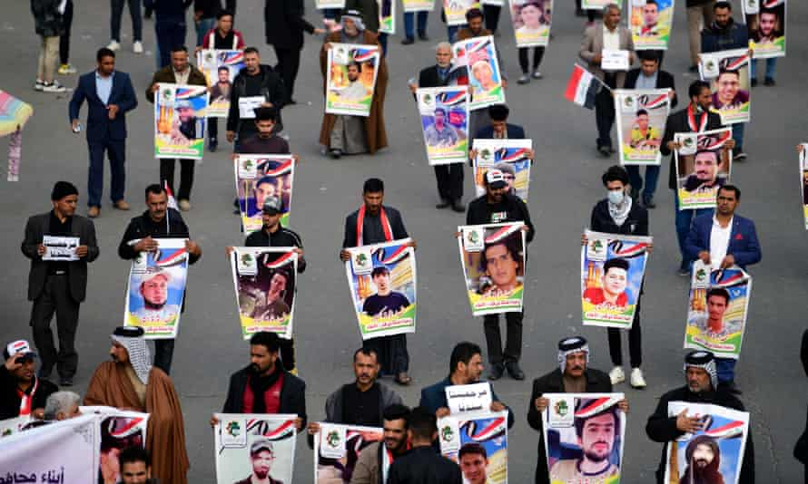 Demonstrators in Baghdad carry the pictures of the victims of protests