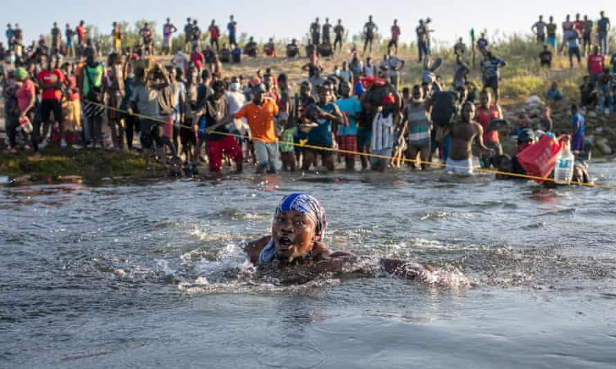 woman is nearly submerged in water as people cross the river