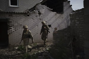 Donetsk, UkraineUkrainian soldiers walk next to a destroyed house near a fighting position on the line of separation from pro-Russian rebels near Donetsk