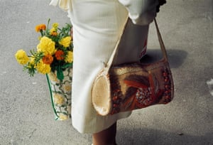 A close-up of a woman carrying a handbag and a shopping bag with flowers in