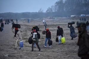 People carry luggage as they make their way towards the meeting points