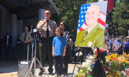The Santa Cruz sheriff, Jim Hart, stands next to a photo of fallen Sgt Damon Gutzwiller, who was shot and killed in Ben Lomond.