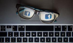 laptop keyboard with glasses reflecting facebook logo