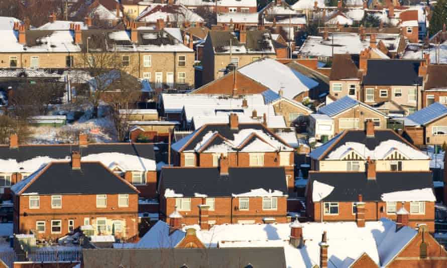 UK homes in winter with snow on their roofs