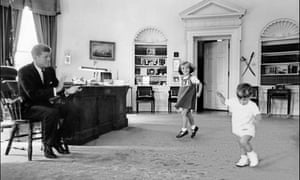 The president watches his children Caroline and John F Kennedy Jr playing in the Oval office.