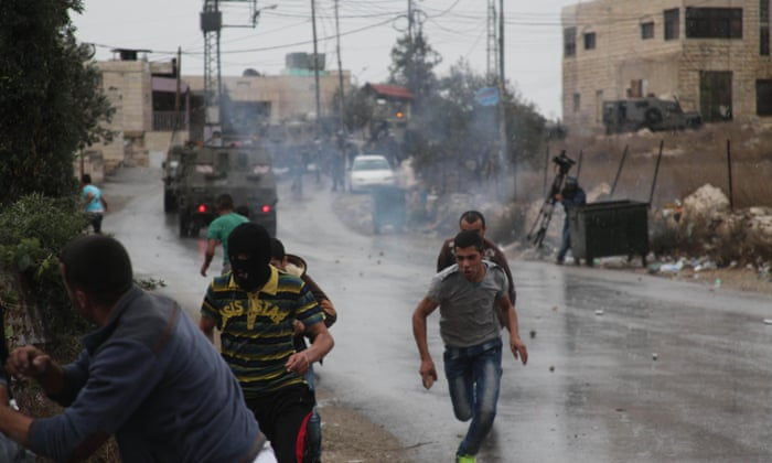 Palestinian protesters run from teargas fired by Israeli soldiers during clashes in the West Bank. Photograph: Emad Drimly/Xinhua Press/Corbis