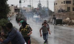 Palestinian protesters run from teargas fired by Israeli soldiers during clashes in the West Bank.
