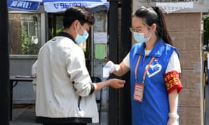 A volunteer checks a resident's temperature at the entrance of a community in Haidian district in Beijing.