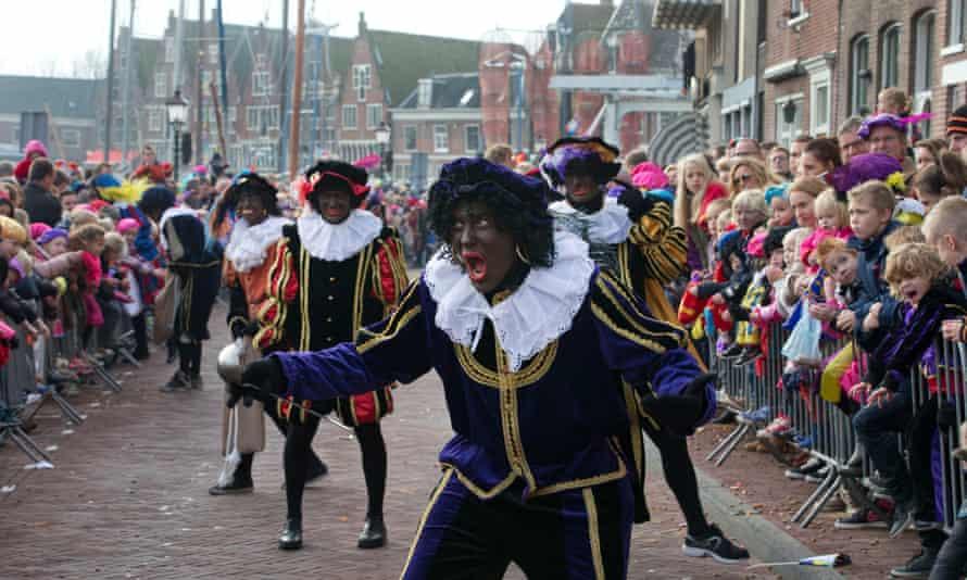 """""""Black Pete"""" jokes with children after arriving with Sinterklaas in Hoorn."""