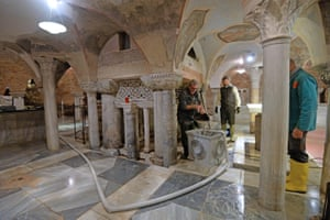 Maintenance workers remove the last of the water in the crypt under the Basilica of San Marco