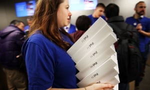 An Apple employee carries iPad Air boxes.