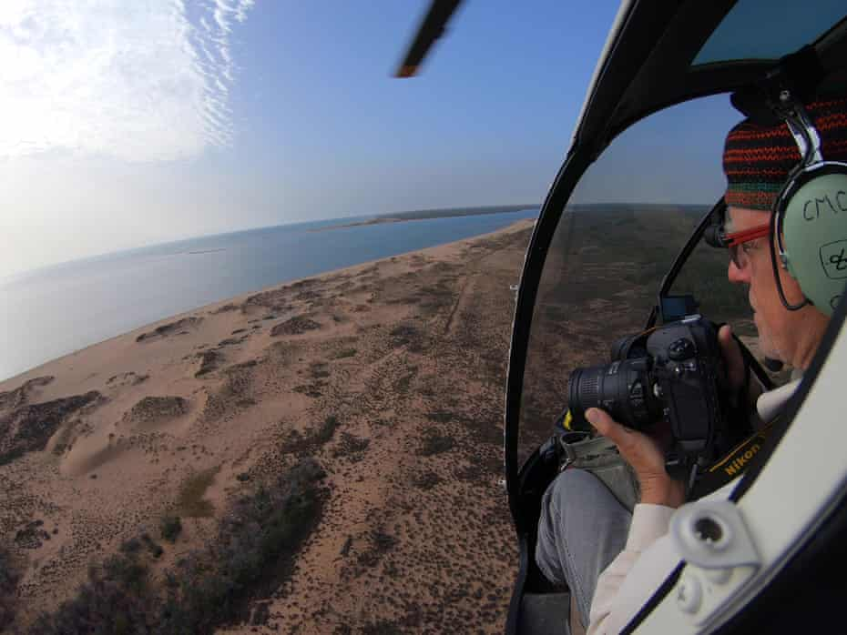 A scientist surveys the Gulf of Carpentaria from a helicopter
