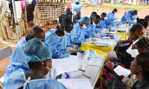 Congolese health workers register people and take their temperatures
