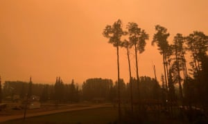 Stellat'en First Nation is shrouded in an orange haze, as smoke continues to drift over from the wildfires into Fraser Lake, British Columbia, Canada, on 14 August.