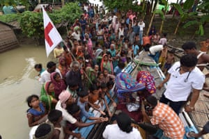 Officials from Jhargaon public health centre distribute medicine to villagers in the flood-hit Sagolikota area of Morigaon district, in India's Assam state